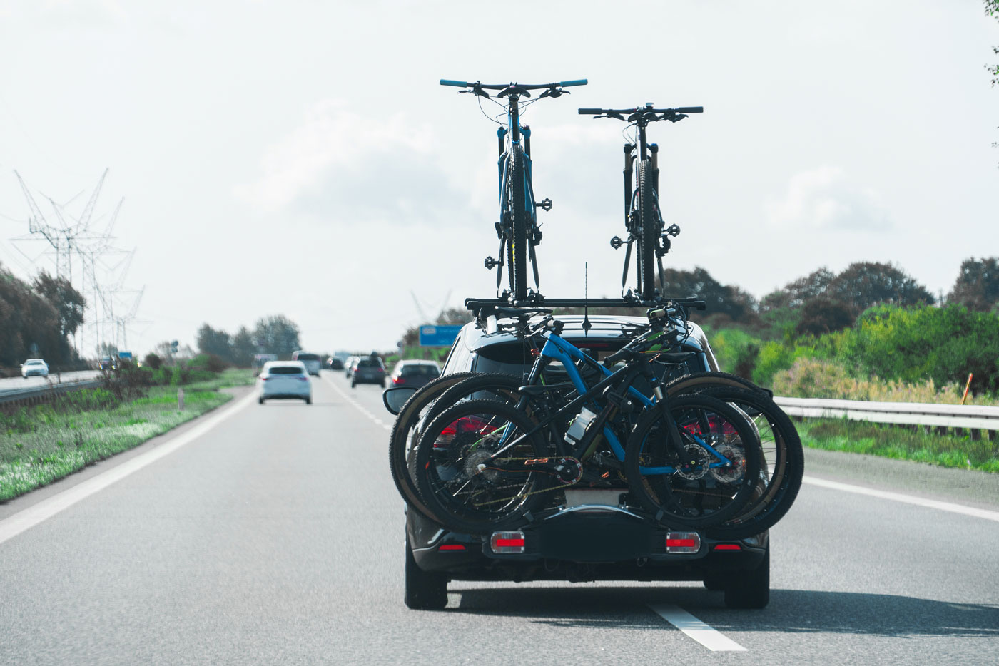 car with bikes mounted on top and from the back hitch