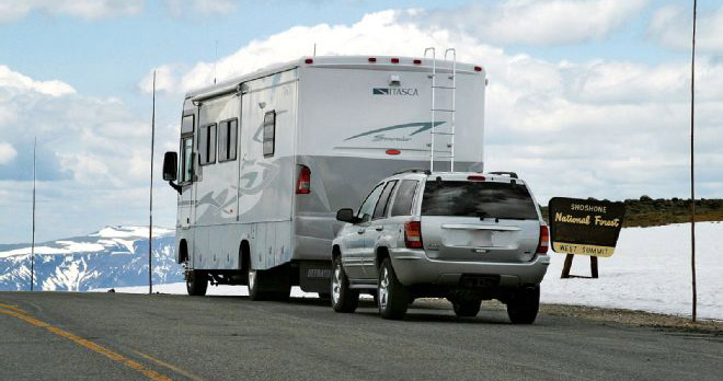 vehicle attached to back of rv driving on the highway